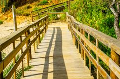 Wooden boardwalk leading to the sandy beach, the path by the sea Stock Photo