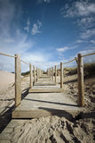 Wooden boardwalk on the sand Stock Image