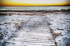 Wooden boardwalk on the sand at sunset Stock Photography