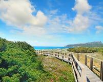 Wooden boardwalk under a cloudy sky in Capo Testa Stock Photos