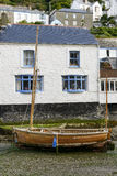 Wooden boat aground and old house, Polperro. Cityscape of the touristic village on southern coast of Cornwall with low tide in the river harbour and old wooden Stock Photography