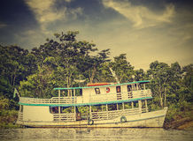 Wooden boat on the Amazon river, Brazil, vintage retro instagram Stock Photos
