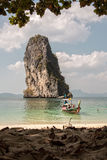 Wooden boat arriving on beach with rocky cliff Royalty Free Stock Image