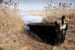 The wooden boat on the bank of the lake in the early spring Stock Photos