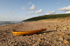 Wooden Boat on the Beach. Wooden boat resting on the beach with the waves crashing in and the sun setting giving a golden colour in the scenic Royalty Free Stock Photography