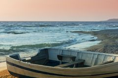 The wooden boat on the beach on sunset. The wooden boat on the beach on the sunset Stock Photo