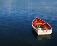 Wooden boat on blue sea. Wooden rowing boat reflecting on blue sea with copy space Royalty Free Stock Photo