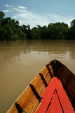 Wooden boat on brown river Royalty Free Stock Photos