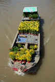 Wooden boat carrying flowers to the floating market in Ben Tre, Vietnam Royalty Free Stock Photos