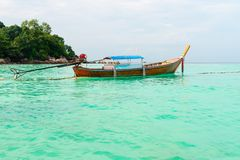 Wooden boat on the clear turquoise sea water. Tourist wooden boat on the clear turquoise sea water with green island on background Stock Photography
