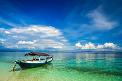Wooden boat on the clear waters of paradise royalty free stock photos