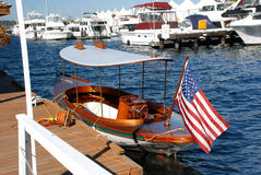 Wooden Boat with cover. Sailboat with cover and American Flag on the water backdropped by other boats Stock Images
