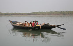 Wooden boat crosses the Ganges River in Sundarbans, West Bengal, India stock photos