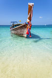 Wooden boat on crystal clear shallow water. Royalty Free Stock Photos