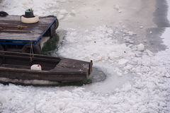 Wooden boat and dock in frozen river on cold winter day Royalty Free Stock Photography