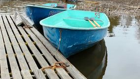 Empty boat on the water. Wooden boat at the dock on the water stock footage