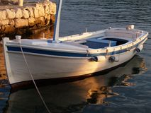 Wooden boat at the docks. A small traditional Croatian wooden boat, docked in calm waters at sunset Royalty Free Stock Image