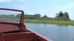 Wooden boat floating near coastal grasses. In summer stock video footage