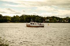 Wooden boat floating on norwegian fjord Royalty Free Stock Photography