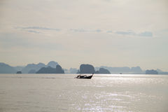 Wooden boat floating on the sea with small mountains background Royalty Free Stock Images