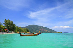 Wooden boat floating on turquoise Andaman sea against blue sky Royalty Free Stock Image
