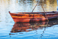 Wooden boat floating on water surface Royalty Free Stock Image