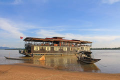 Wooden boat in front of The Vat Phou Cruise 2 decks floating hot Royalty Free Stock Photos