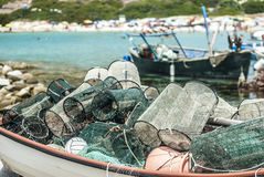 wooden boat full of fishing nets with a beach, blue sea and a fi Royalty Free Stock Image