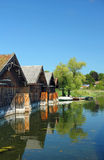 Wooden boat houses reflecting in the water of lake staffelsee, b Royalty Free Stock Photo
