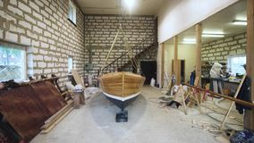 Wooden boat inside workshop. Wooden boat with sail mast indoor workshop. steadicam wide angle. Homemade Sailbaot ready to move in sea, lake, or river. Big hobby stock video