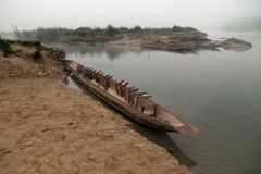 A wooden boat with inverted seats near the river bank, early morning, Chitwan, Nepal. Royalty Free Stock Photography