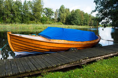 Wooden boat at jetty. A motor boat at jetty in a river royalty free stock photos