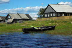 Wooden boat on the lake bank in small village Stock Photos