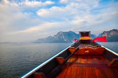 Wooden boat in the lake with beautiful sky. And mountains Stock Images