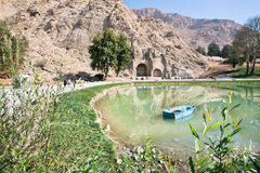 Wooden boat in the lake of oasis near the historical landmarks of Taq-e Bostan Stock Photography
