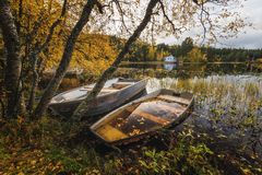 Wooden boat by the lake shore, Norway, beautiful autumn time, calm water stock photo