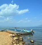 Wooden boat on a lakeshore, Large Prespa Lake in Greece. Capture of a wooden traditional boat in the large Prespa Lake in Greece Royalty Free Stock Photo