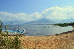 Wooden boat on a lakeshore, Large Prespa Lake in Greece. A traditional wooden boat on the lake shore of the Large Prespa Lake in Greece. This lake shore is royalty free stock images