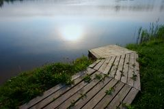 Wooden boat landing pier by lake at sunset stock image