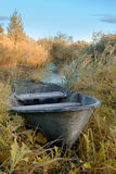 A wooden boat lies among the dry grass near the pond.  Stock Photo