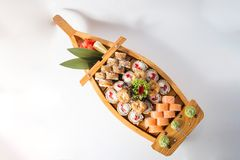 Wooden boat with lots of sushi with ginger and wasabi.  stock photography