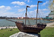 Wooden boat with masts for sails. Slavyansk-on-Kuban, Russia - March 19, 2018: Wooden boat with masts for sails. The model of the ship in front of the lake in Royalty Free Stock Photos