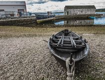 Wooden Boat Moored at Low Tide, Lerwick, Shetland. Wooden rowboat with two sets of oars moored at low tide on a pebble shore in Lerwick, Shetland Stock Photography