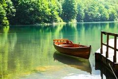 Wooden boat on mountain lake Stock Photo