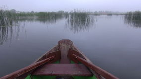 Wooden boat with oars on lake and mist. Wooden boat with oars on lake and morning mist stock video