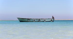 Wooden boat on Paradise island in Red See, Egypt with boatman royalty free stock photography