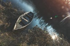 Wooden boat peacefully resting on the water of autumn river at t Royalty Free Stock Photo