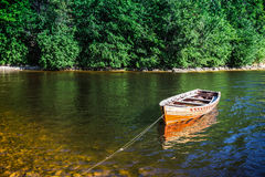 Wooden boat on the river bank Stock Photos