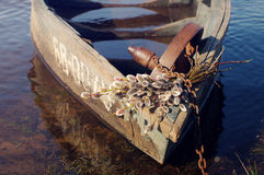 Wooden boat on the river with a bouquet of spring branches of a willow Stock Photography
