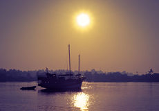Wooden Boat on River in the Sunrise Stock Photo